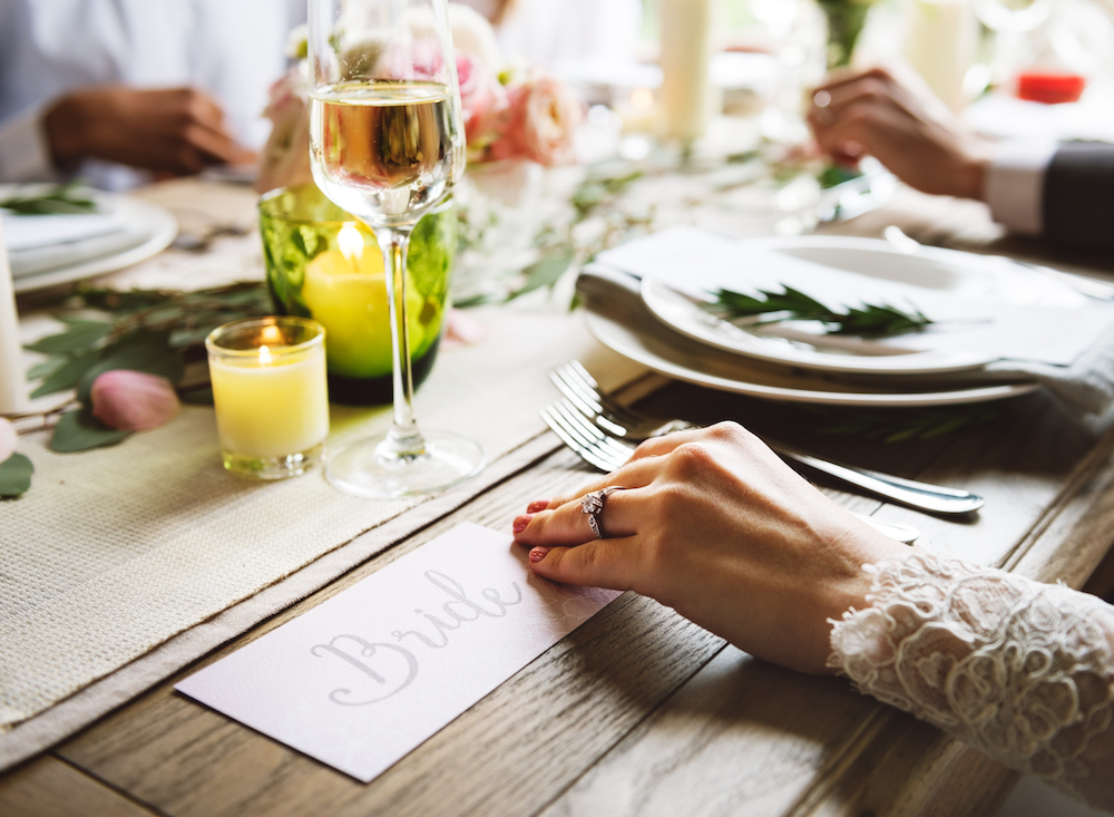 Newlyweds are enjoying dinner at their wedding reception after a beautiful ceremony.